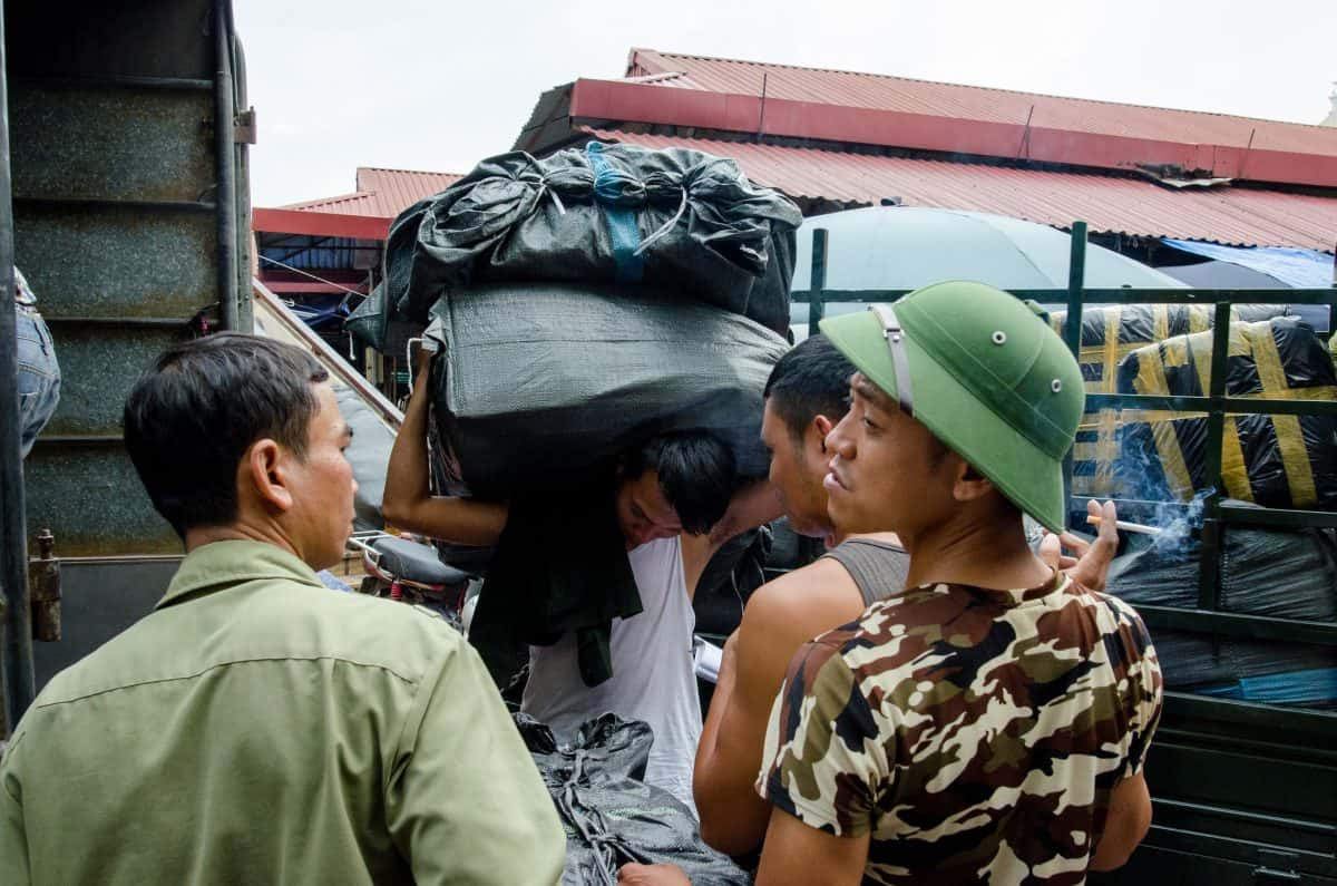 Men and Women unload a truck with goods at Dong Xuan Market, Hanoi.